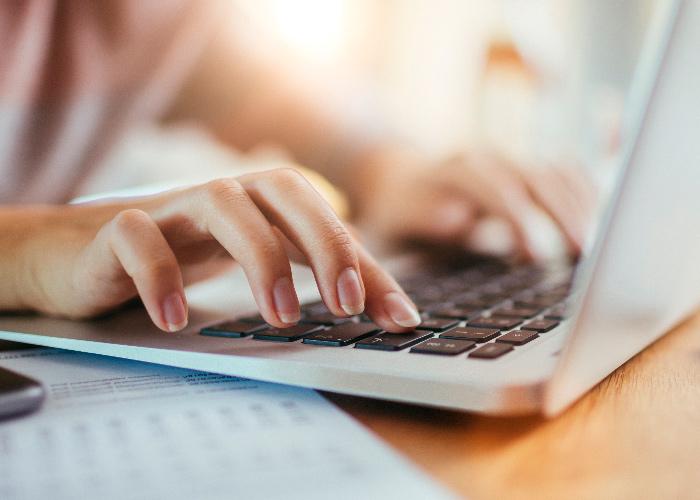 Frau bedient Laptop - goldblau